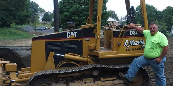 Picture of Bob Marki, President of L. Marki and Son, Inc. in front of a bulldozer.