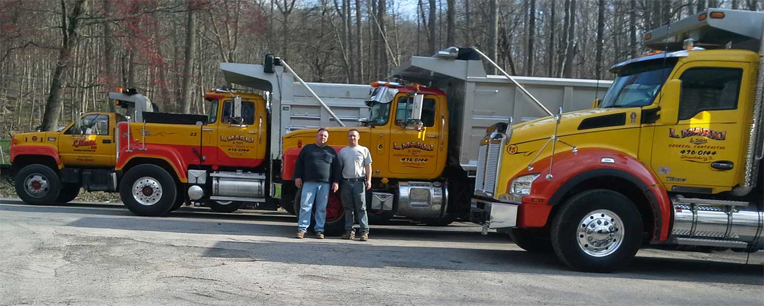 Bob-and-Rob-Marki-in-front-of-fleet-of-trucks