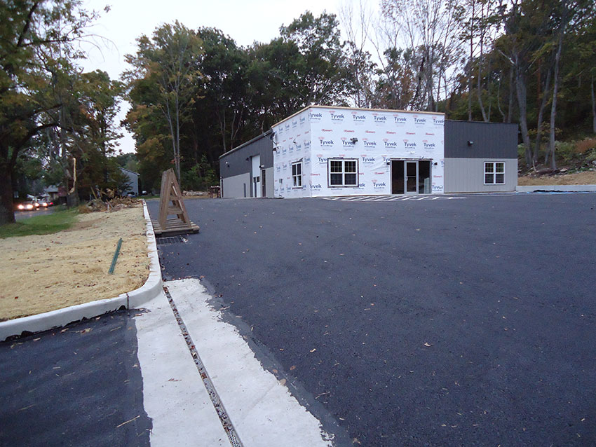 A picture of the building with freshly paved parking lot and areas seeded for grass