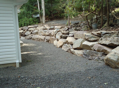 a rock wall with a shaled area surrounding it