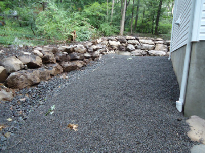 A rock retaining wall with a shale mulch around