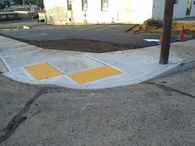 Picture of the corner sidewalk installed at second parking lot with metal handicapped accessable slabs.