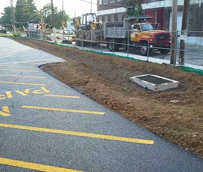 Picture of the side of the larger parking lot, showing the top soil that was spread, the drain placed, and the sidewalk installed.
